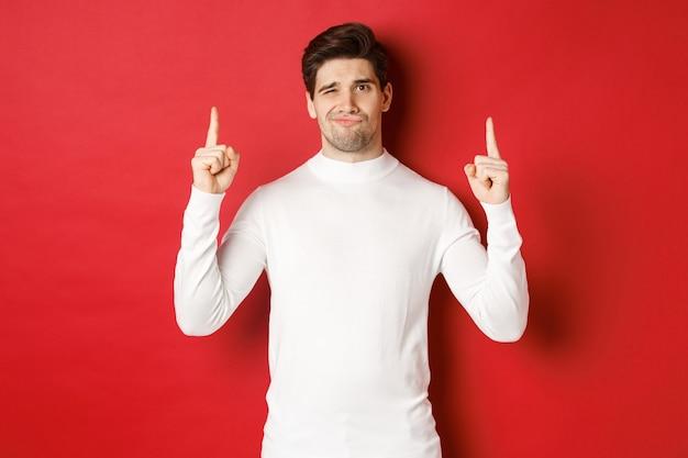 冬の休日の概念。失望したハンサムな男は、白いセーターの赤い背景の上に立って、指を上に向けて顔をゆがめた、プロモーションをお勧めしません。