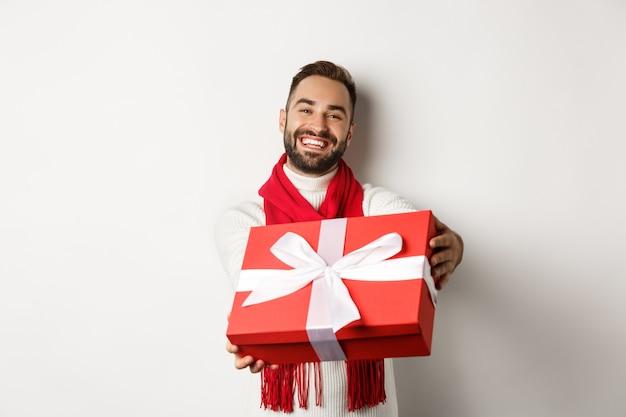 冬の休日の概念。贈り物を与えるハンサムなボーイフレンド、メリークリスマスと新年あけましておめでとうございます、白い背景の上に立って