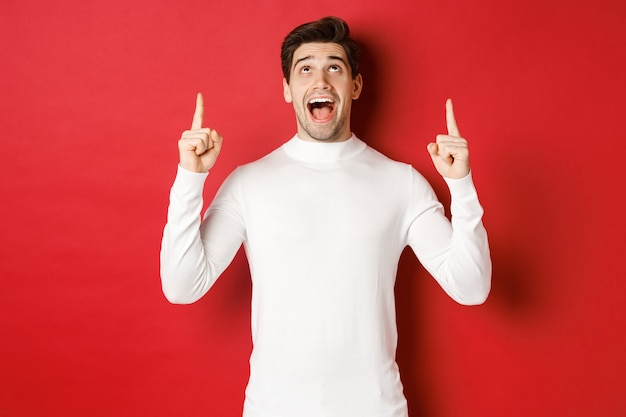 冬の休日の概念。クリスマスの発表に反応し、コピースペースを指差して見上げ、赤い背景の上に立っている驚いたハンサムな男の画像