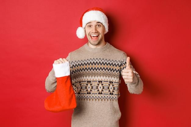 Концепция зимних праздников, нового года и торжества. веселый красавец в новогодней шапке и свитере, показывает рождественский чулок с конфетами и подарками, показывает палец вверх