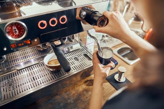 커피 메이커를 사용하여 카페에서 우유를 스팀하는 여성 바리 스타의 개념.