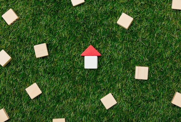나무 장난감 집과 푸른 잔디에 주위 다른 블록의 개념.