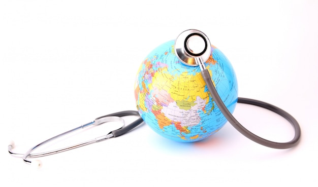 世界環境デーのコンセプト。白で隔離される聴診器で地球