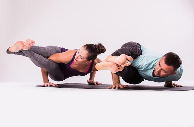 ヨガの練習の概念。白い背景の上のヨガの位置に若い健康なカップル