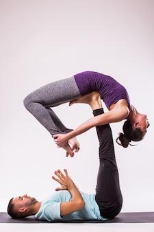 요가 운동의 개념. 흰색 바탕에 요가 위치에 젊은 건강 한 부부