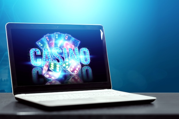 Concept for online casino, gambling, online money games, bets. neon casino chips, casino inscription, poker cards, dice fly out of the laptop.