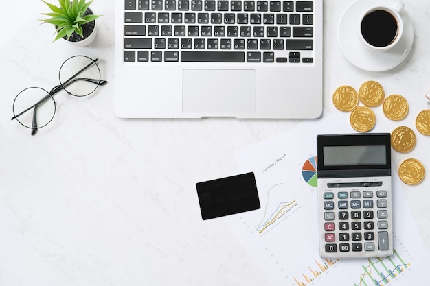 Concept of online payment with credit card with smart phone, laptop computer on office desk on clean bright marble table background, top view, flat lay