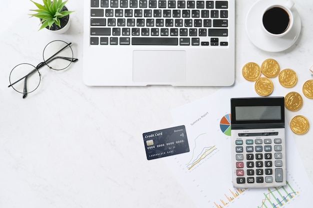 Concept of online payment with credit card with smart phone, laptop computer on office desk on clean bright marble table background