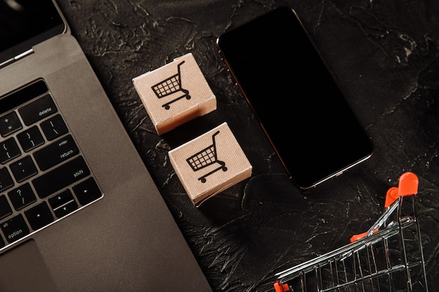 Concept of online shopping. boxes, laptop and smartphone on a grey table.