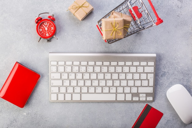 Concept online shopping buying presents. red credit card, keyboard and mouse