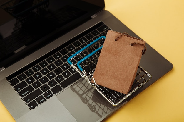 Concept of online shopping. paper shopping bag and cart on keyboard of laptop isolated on yellow