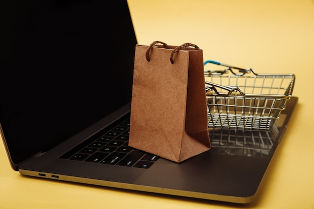 Concept of online shopping. paper shopping bag and cart on keyboard of laptop.