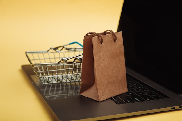Concept of online shopping. shopping bag and cart on keyboard of laptop