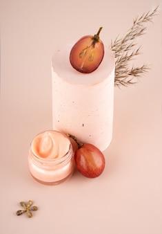 가정에서 피부 관리를 위한 크림에 있는 개념 유기농 추출물 천연 포도 씨 오일. 분홍색 배경에 수제 석고 연단, 받침대, 말린 꽃이 있는 창의적인 정물 구성. 복사 공간