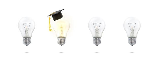 Концепция из коробки. шапка выпускника на светящейся лампочке. концепция образования и идеи.