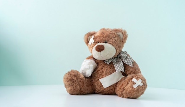 A concept of pain and illness problem, teddy bear toy wrapped in bandage, accident injury