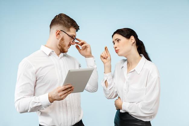 Concetto di partnership nel mondo degli affari. giovane uomo emotivo e donna su sfondo blu in studio. le emozioni umane e il concetto di partnership