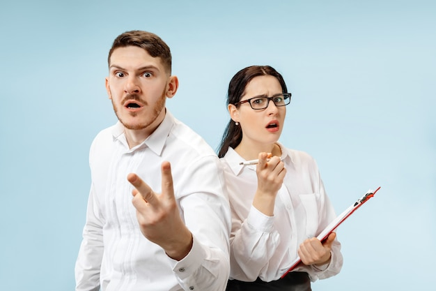 Concept of partnership in business. young emotional man and woman against blue background at studio. human emotions and partnership concept