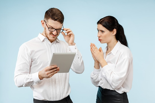 Concetto di partnership nel mondo degli affari. giovane uomo emotivo e donna su sfondo blu