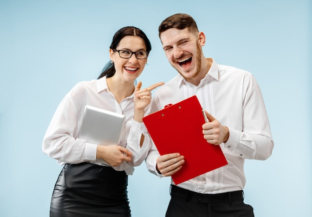 Concept of partnership in business. young happy smiling man and woman standing against blue background at studio