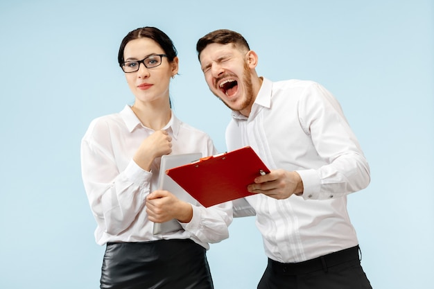 Concept of partnership in business. young happy smiling man and woman standing against blue wall