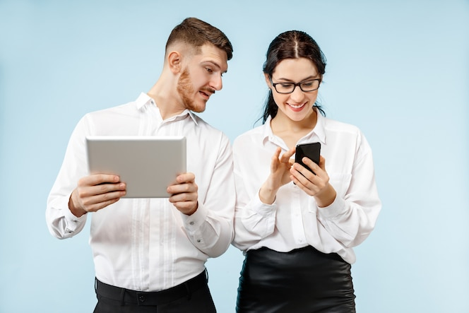 Concept of partnership in business. young happy smiling man and woman standing with phone and tablet against blue background at studio