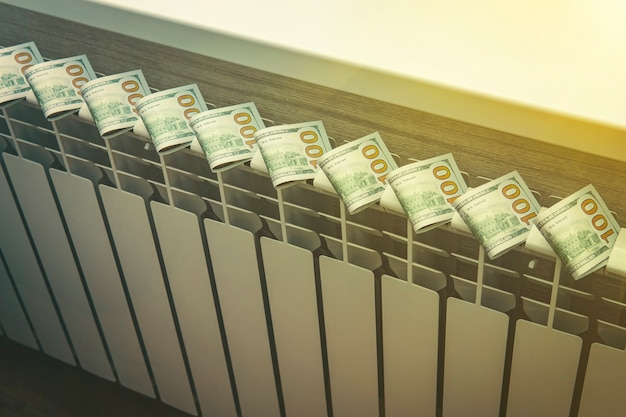 Concept of paying for heating in homes with a cold climate. closeup dollar bills on radiator