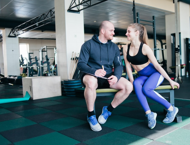 The concept of personal training. instructor notes in notebook results training sporty blonde woman sitting on a bench