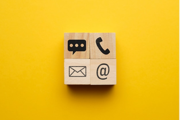 The concept of phone contacts, email, instant messengers with icons on wooden blocks.