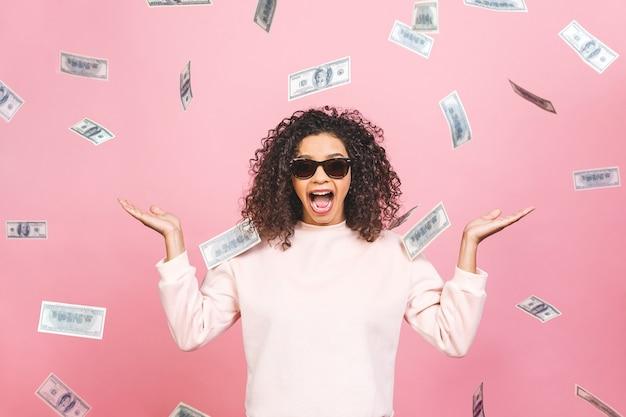Фото концепции жизнерадостной афро-американской женщины, стоящей под дождем с деньгами, изолированными на розовом фоне.