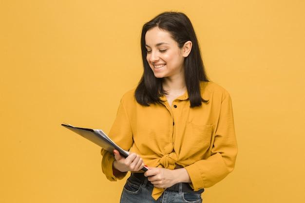 Фото концепции бизнес-леди держит документы. носит желтую рубашку, изолированный желтый цвет фона.
