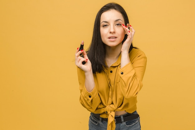 かわいい女性のコンセプト写真は化粧をし、口紅を保持します