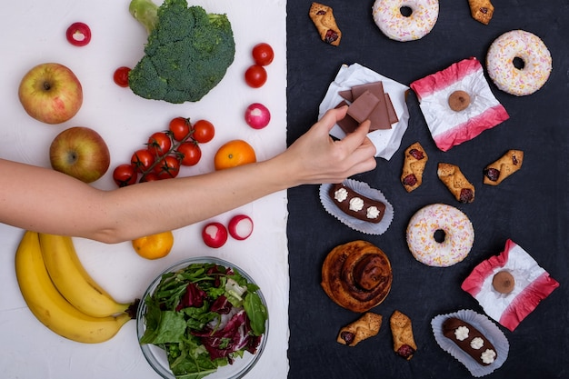 건강하고 건강에 해로운 음식의 컨셉 사진. 과일 및 야채 vs 도넛, 과자 및 햄버거