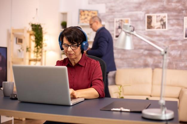 현대 기술을 사용하는 노부인의 컨셉 사진. 그는 무선 헤드폰과 노트북을 사용합니다.