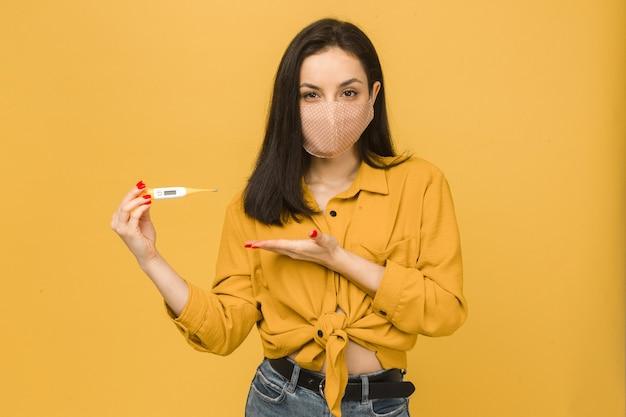 フェイスマスクの病気の女性の概念写真は温度計を保持します