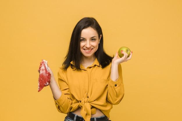 Концептуальное фото сладкой самки выбирает между мясом и яблоком. носит желтую рубашку, изолированный желтый цвет фона.