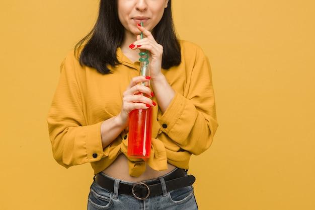 Концептуальное фото сладкой женщины пьет коктейли, лето. носит желтую рубашку, изолированный желтый цвет фона.