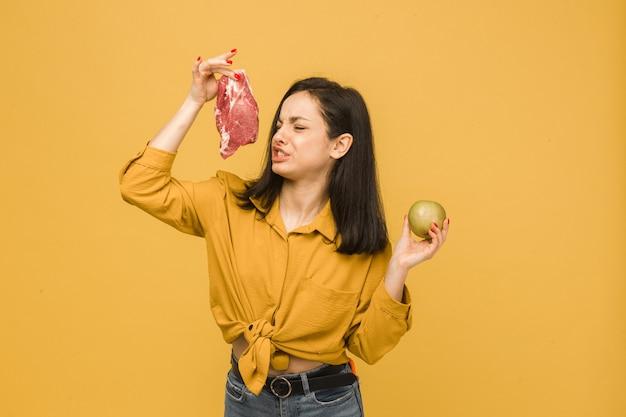 Концептуальная фотография сладкой вегетарианки, которая пахнет мясом и, похоже, ей это не нравится. носит желтую рубашку, изолированный желтый цвет фона.
