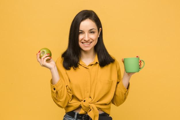 Фото концепции молодой женщины есть яблоко и что-то пить. носит желтую рубашку, изолированный желтый цвет фона.
