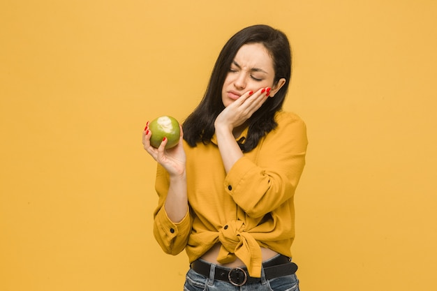 Фото концепции молодой женщины, едящей яблоко и получившей зубную боль. носит желтую рубашку, изолированный желтый цвет фона.