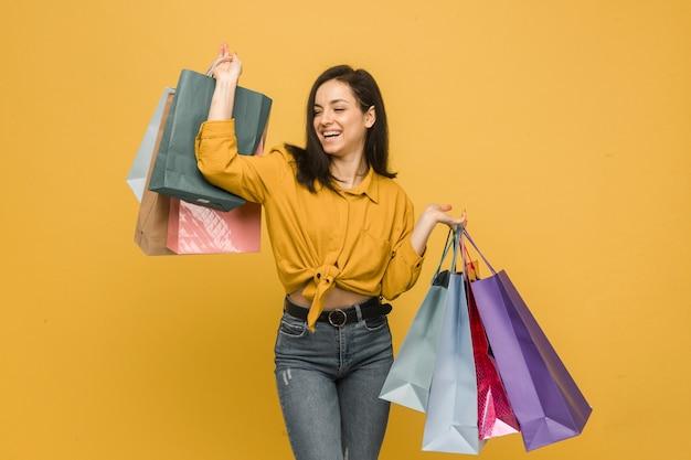 若い女性のコンセプト写真は買い物袋を持って、服を買う