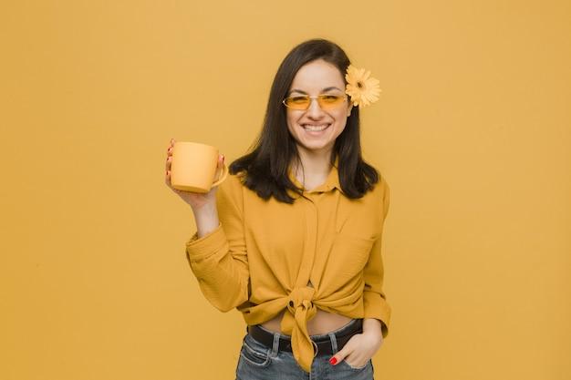 眼鏡をかけた若い女性と髪の花のコンセプト写真、飲み物を保持し、春の時間を感じます