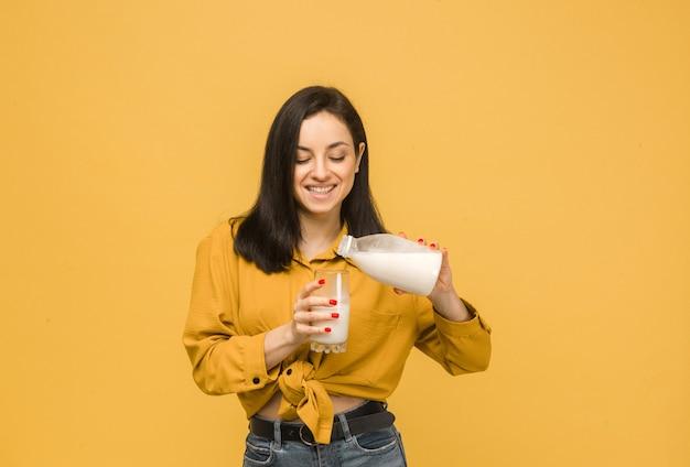 Концепция фото молодой женщины наливает молоко в стакан. носит желтую рубашку, изолированный желтый цвет фона.