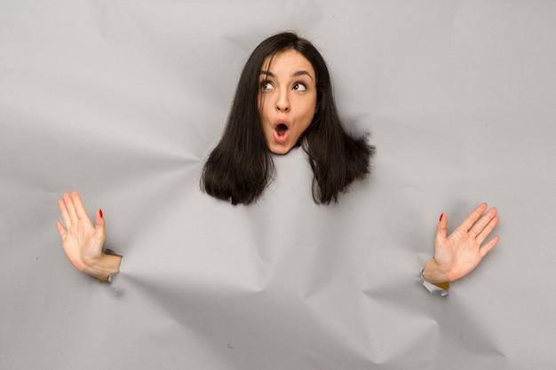 Концептуальное фото молодой женщины, разрывающей бумагу и выглядывающей из отверстия, интересующейся коммерческим предложением на копировальном пространстве, изолированной серым цветом фона.