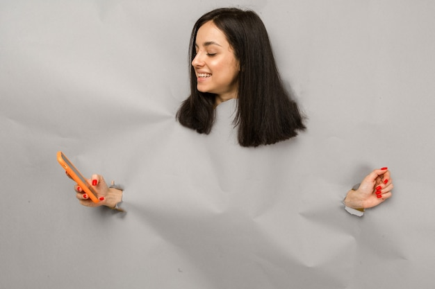 若い女性が紙を引き裂き、穴をのぞき、スマートフォンを持って、孤立した灰色の背景のコンセプト写真。