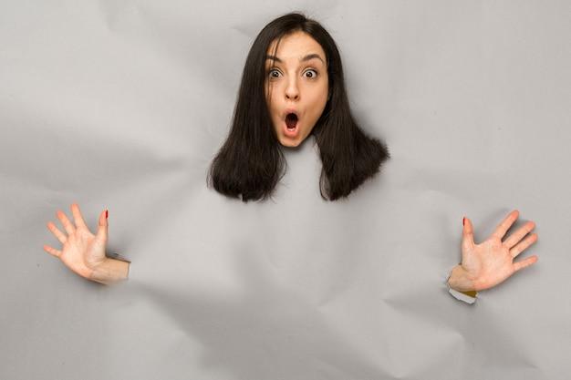 Концептуальное фото молодой женщины, разрывающей бумагу и выглядывающей из отверстия, потрясенной коммерческим предложением на копировальном пространстве, изолировал серый цвет фона.