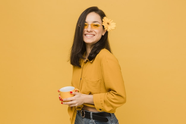 Concept photo of young female in glasses and flower in hair, holds drink, feeling spring time. wears yellow shirt, isolated yellow color background