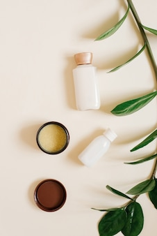 Concept of plant-based, organic cosmetics. bottles with body or face cream, solid cocoa butter in an open jar and a branch of a tropical plant on a beige background.