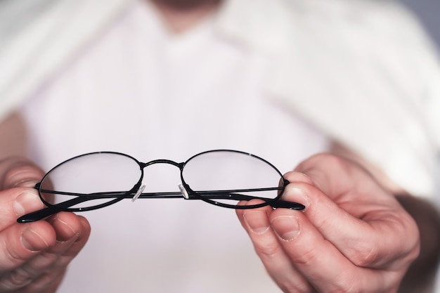 The concept of poor vision. hold a contact lens and glasses in hand. a poster for advertising glasses and lenses.