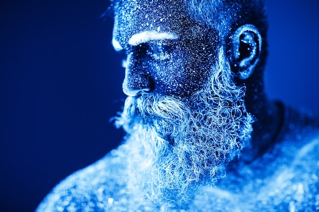Concept. portrait of a bearded man. the man is painted in ultraviolet powder.